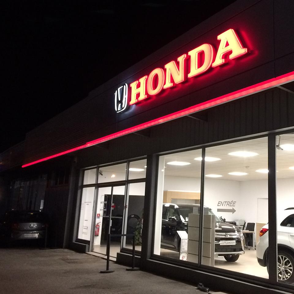 Honda logo lit up at night by Visotec